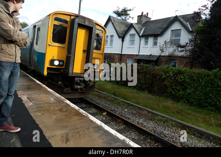 Young man waiting on Heart of Wales line platform for an Arriva train to Swansea  Llanwrda station Carmarthenshire - Stock Photo