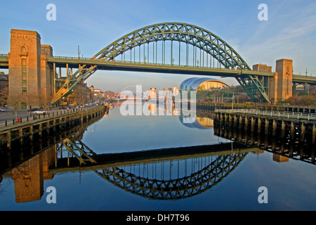 Newcastle upon Tyne's iconic Tyne Bridge is reflected in the River Tyne, with The Sage building and Gateshead Millenium - Stock Photo