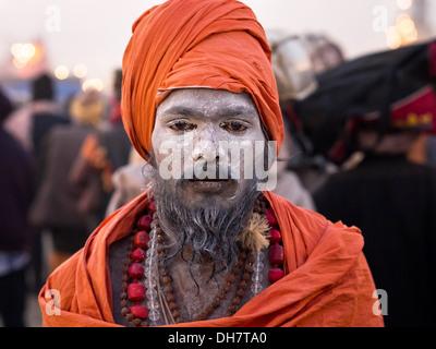 Orange-robed Indian sadhu at Kumbh Mela 2013, the world's largest religious festival in Allahabad, India. - Stock Photo
