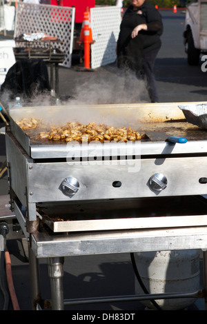 Grilled Chicken cooking outside on a gas grill at an outdoor event - Stock Photo