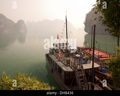 A view of the spectacular limestone karst formations and boats moored  in Halong Bay, Vietnam. - Stock Photo