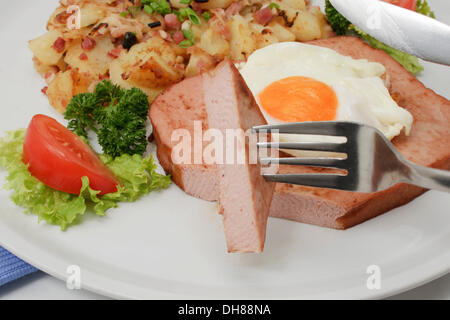 Leberkaese with fried egg and fried potatoes, Bavarian speciality - Stock Photo