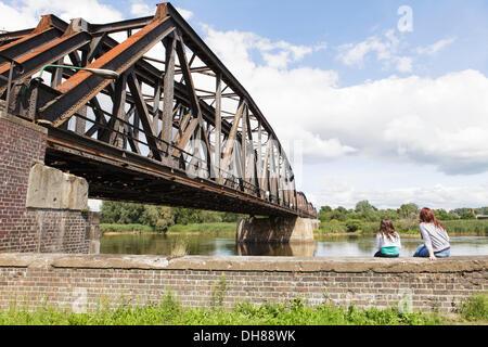 Railway bridge over the border river Oder, Polish-German border, Kuestrin to Kostrzyn, two girls sitting on the - Stock Photo