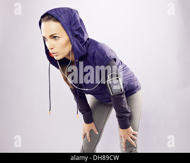 Young caucasian woman taking breath after jogging. Female athlete resting with hands on knees and looking away - Stock Photo