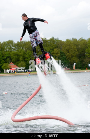 A man is giving a show how to keep in balance, and shows what you can do with the new sensation called flyboarding. - Stock Photo