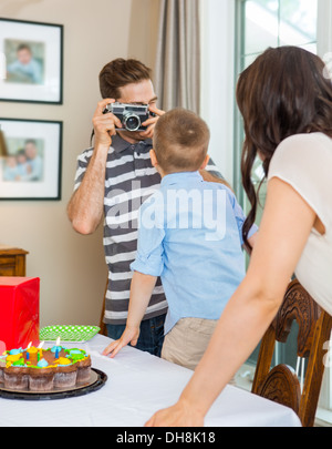 Father Taking Picture Of Birthday Boy And Woman - Stock Photo
