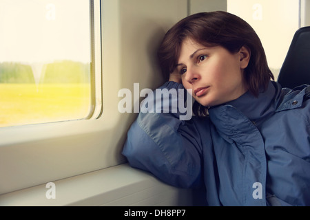 Young woman is traveling by train, looking to the window - Stock Photo