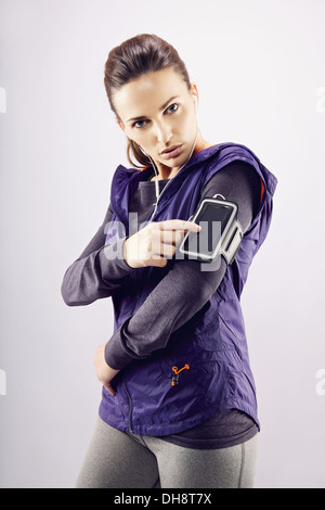 Fitness woman wearing earphones and mp3 player. Female runner listening music on grey background - Stock Photo