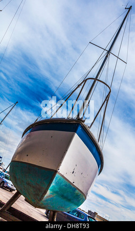 Close-up of the hull of a yacht in dry dock awaiting maintenance and repair taken on the diagonal. - Stock Photo