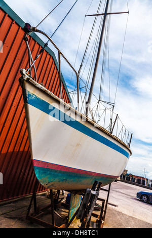 Close-up of the hull of a yacht in dry dock awaiting maintenance and repair. - Stock Photo
