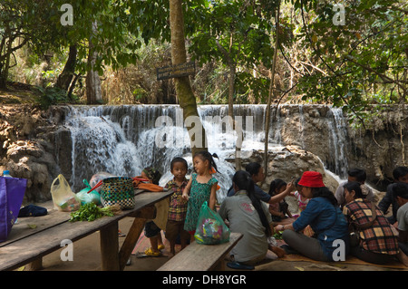Horizontal portrait of an Asian family having a picnic by the picturesque Kuang Si Falls in Laos. - Stock Photo
