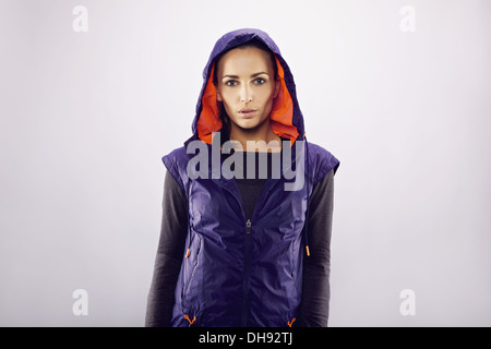 Portrait of pretty female runner wearing sportswear looking at camera. Beautiful and fit young woman wearing hoodie - Stock Photo