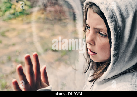 Young Girl Looking out of Window - Stock Photo