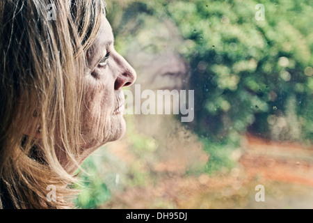 Senior Lady looking out of Window - Stock Photo