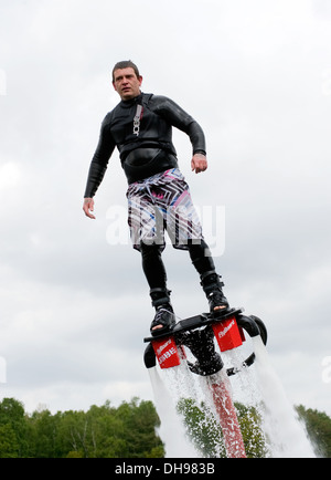 A man is giving a show how to keep in balance, and shows what you can do with the new sensation called flyboarding - Stock Photo