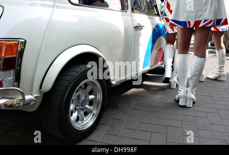1960's style models in  white boots and union jack mini skirts in front of a classic white mini car - Stock Photo