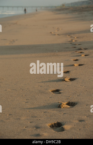 Footprints in the sand cast long shadows at daybreak on Manhattan Beach in California. - Stock Photo