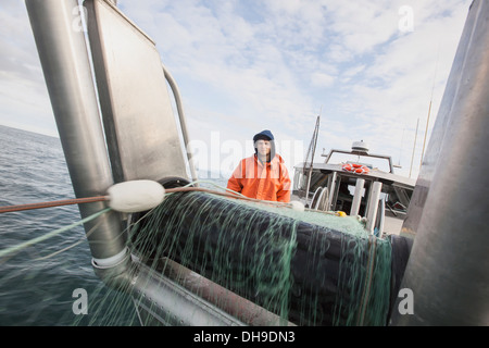 A Young Deckhand Watches And Waits For Fish As The Gillnet Is Pulled On Board. Salmon Fishing On The Copper River - Stock Photo
