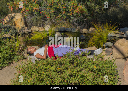 A woman sits on a wooden bench and meditates by a small pond with running water at Meditation Mount, Ojai, California. - Stock Photo