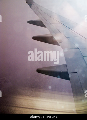 airplane wing photographed through a dirty window over a snowy field. - Stock Photo