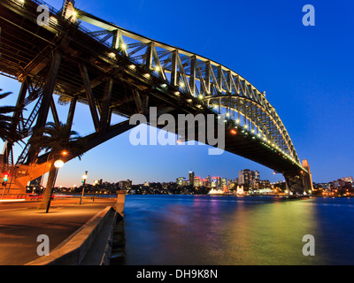 sydney harbour bridge side view of illuminated arch with lights reflection in harbour water at sunset - Stock Photo