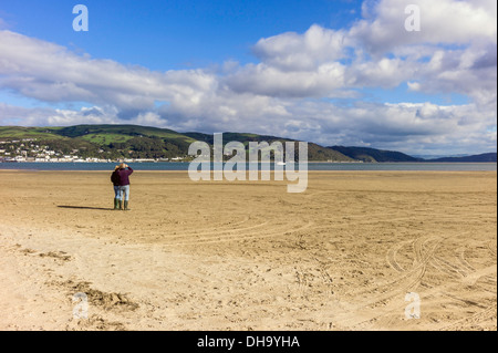 Adult male and female stand in autumn sunlight on Ynyslas sandy beach watching a sail boat motor up the river Dovey - Stock Photo