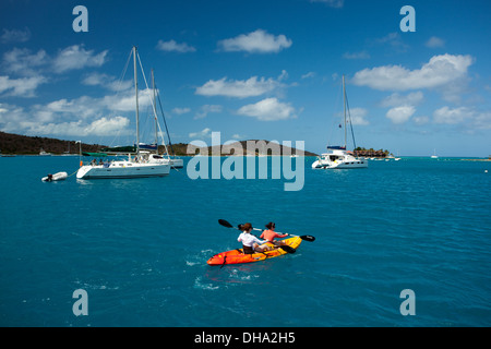 Two people paddle past large white sailboats in Caribbean Sea in the British Virgin Islands on a sparkling summer - Stock Photo