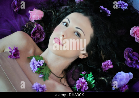Portrait of a young beautiful woman lying on bed - Stock Photo