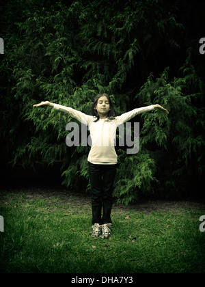 Girl, arms out, eyes closed, conifers - Stock Photo