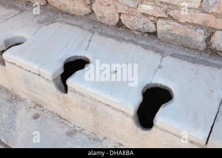 Ancient roman communal toilets at Ephesus Turkey - Stock Photo
