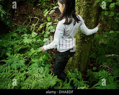 Girl walks in woods. - Stock Photo