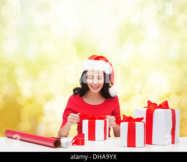 woman in santa helper hat with many gift boxes - Stock Photo