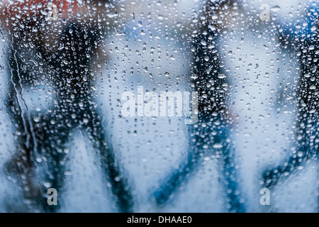 A Window Covered With Rain Drops And Silhouettes Of People Walking By On The Outside - Stock Photo
