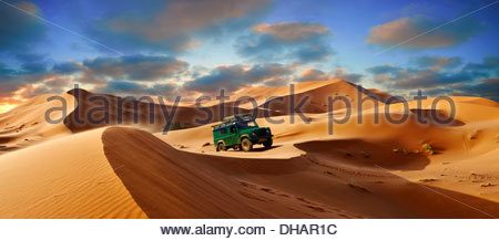 4 x4 Landrover Defnder on the Sahara sand dunes of erg Chebbi at sunset , Morocco, Africa - Stock Photo