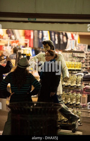 Tourists Pose with a statue of Elvis at a souvenir shop on Hollywood Blvd in Hollywood California - Stock Photo