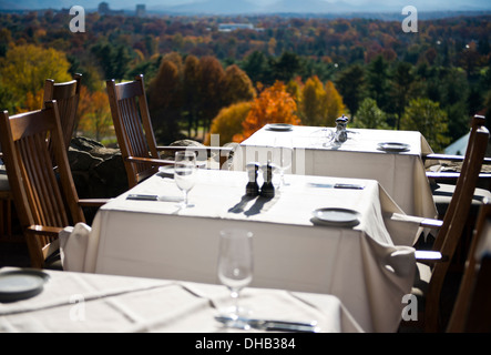 Outdoor dinning tables and settings at the Grove Park Inn Asheville North Carolina with autumn foliage view - Stock Photo