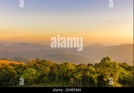 The cardamom Hills at sunset and the lake on the horizon at Periyar wildlife sanctuary in Kerala, India. - Stock Photo