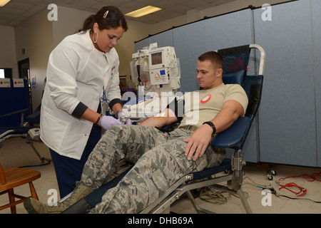 Kay Arroyo with the American Red Cross removes the tubes from the arm of U.S. Air Force Staff Sgt. Tyler Kellogg - Stock Photo
