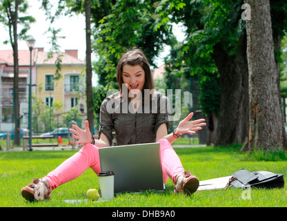 Happy young woman in front of a latop siting on grass outside in an urban park - Stock Photo
