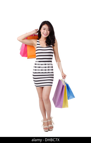 Young woman in a striped dress holding shopping bags - Stock Photo