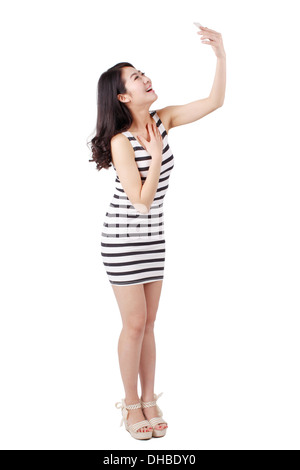 Young woman in a striped dress taking photo,using a cell phone - Stock Photo