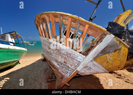 Brazil, Bahia: Boat lying on the beach for restauration in Praia do Forte - Stock Photo