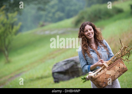 A young woman carrying a basket of freshly harvested garlic and vegetables. Stock Photo