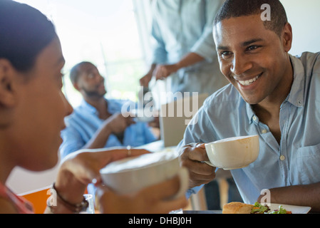 A group of men and women in a cafe, eating and drinking and enjoying each other's company. - Stock Photo