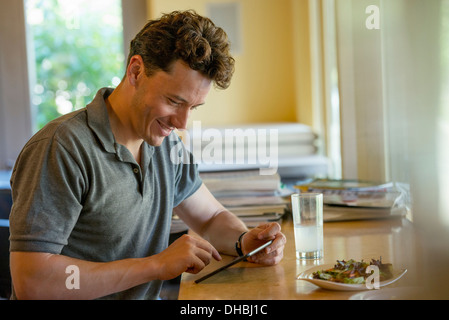 A person sitting alone in a cafe. A  man using a digital tablet. - Stock Photo