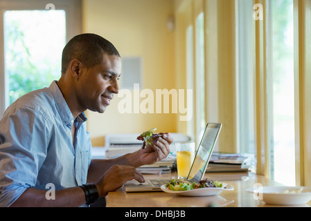 A person sitting alone in a cafe. A man working on a laptop. - Stock Photo