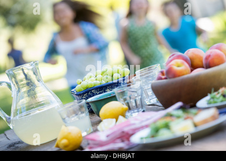 A summer buffet of fruits and vegetables, laid out on a table. Children running in the background. - Stock Photo