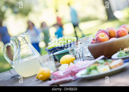 A summer buffet of fruits and vegetables, laid out on a table. People in the background. - Stock Photo