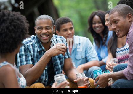 A group of men and women outdoors enjoying themselves. - Stock Photo