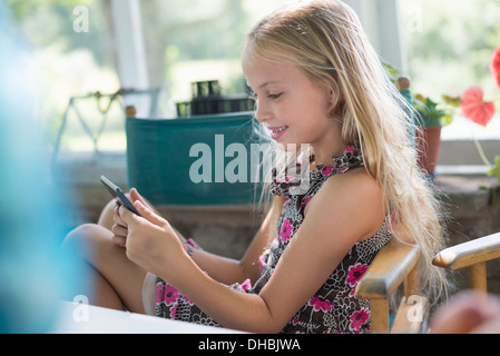 A young girl in a flowered dress using a digital tablet. Sitting at a table. - Stock Photo